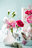 Bouquet of pink carnation in glass vase on light turquoise wooden background. Mothers day, birthday greeting card. Copy space.