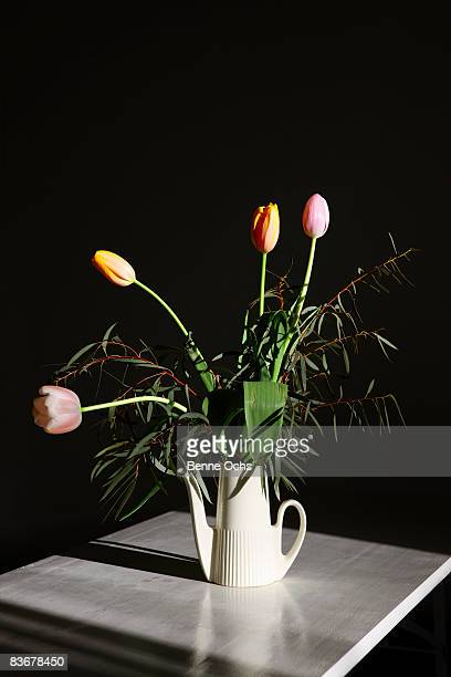A bouquet of tulips in a watering can on a table, still life