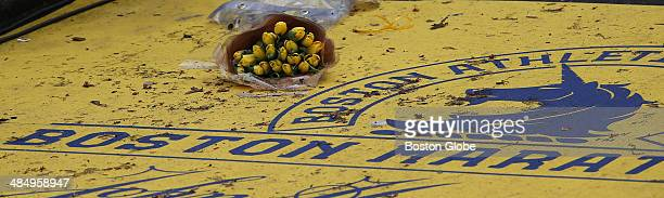 A bouquet of yellow flowers were placed on the finish line of the Boston Marathon route near the BAA logo on April 15 to commemorate the one year...