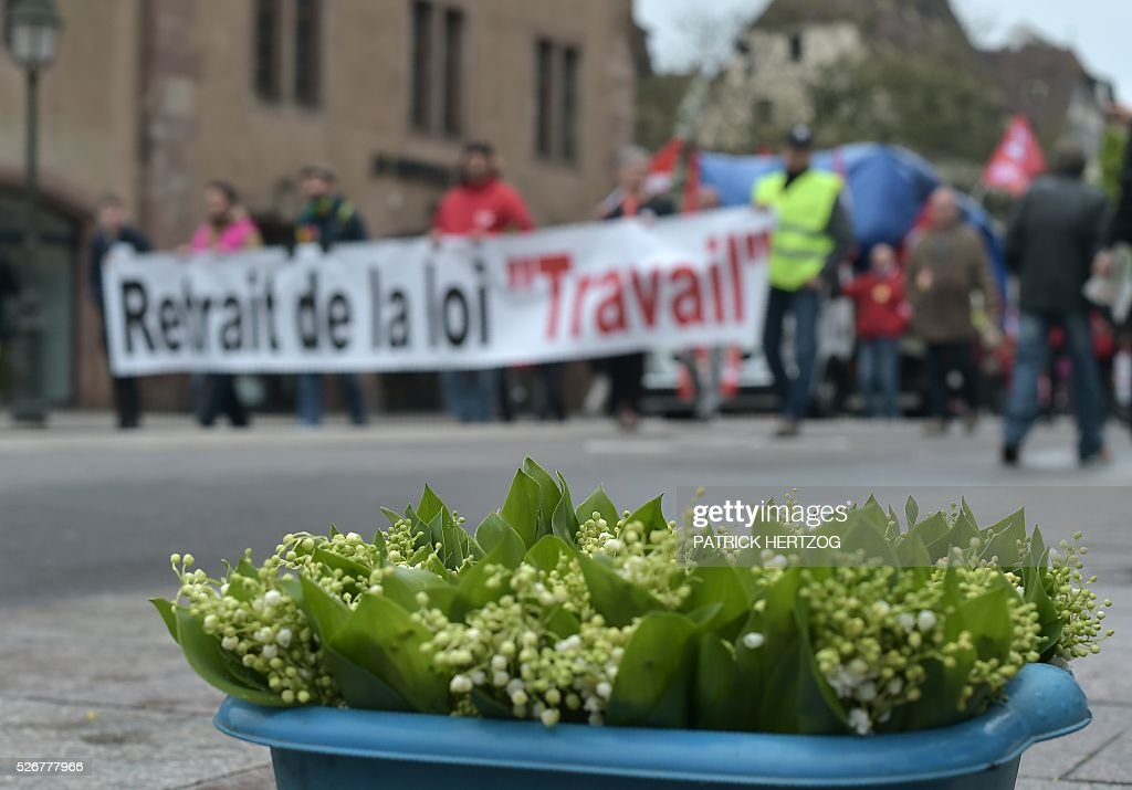 Bouquets of lily of the valley are pictured as participants march with a banner reading 'Withdrawal of the labour law' during the traditional May Day rally in Strasbourg, eastern France, on May 1, 2016. / AFP / PATRICK