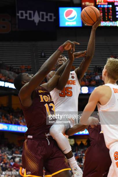 Bourama Sidibe of the Syracuse Orange drives to basket defended by TK Edogi of the Iona Gaels during the second half of play between the Syracuse...