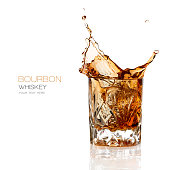 Bourbon whiskey splash in an elegant glass cut glass isolated on white background with copy space for text