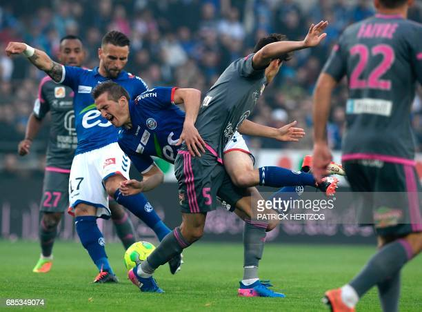 Bourg en Bresse's French midfielder Kevin Hoggas vies for the ball with Strasbourg's Belgian forward Baptiste Guillaume and Strasbourg's French...