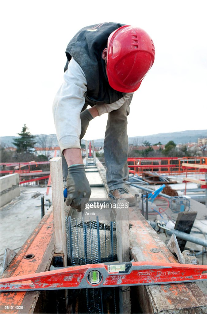 BourglesValence Building of a center dedicated to early childhood Construction workers at work outside A worker smoothes a concrete wall with a trowel