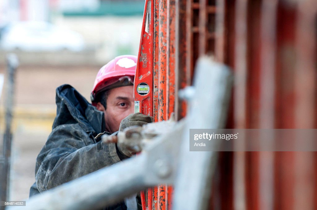 BourglesValence Building of a center dedicated to early childhood Construction workers at work outside here a worker checks a frame with a water level