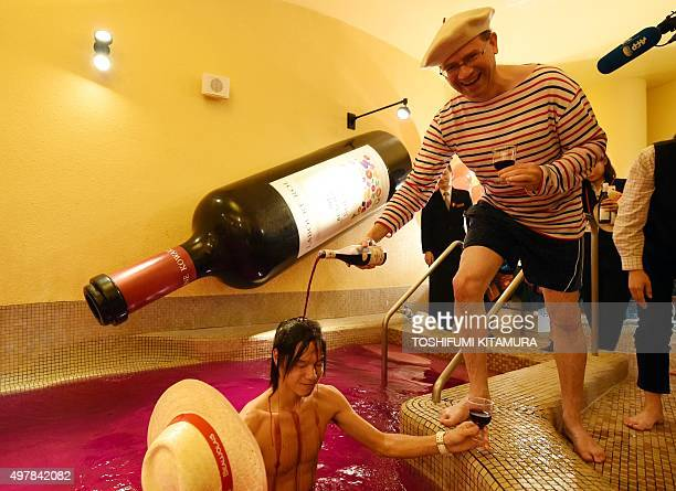 Bourgogne wine maker LaboureRoi Asia Pacific general manager Martin Romeijn pouts 2015 Beaujolais Nouveau wine over a guest at the wine spa in the...