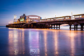 The lights of Bournemouth Pier at night reflected in the wet sand on the beach. Dorset  England UK Europe.