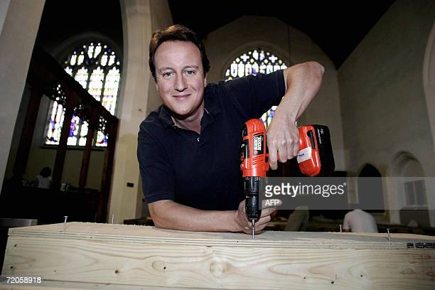 Leader of the Conservative Party David Cameron poses with a drill during a visit of St Mary's Church in Bournemouth 01 October 2006 The church was...