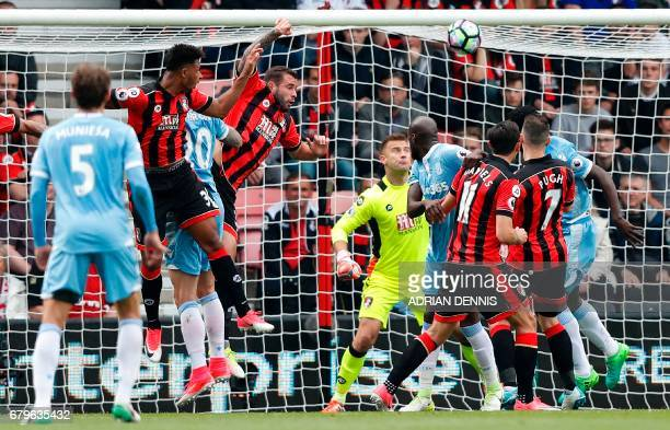 Bournemouth's French midfielder Lys Mousset watches the ball after heading to score an own goal during the English Premier League football match...
