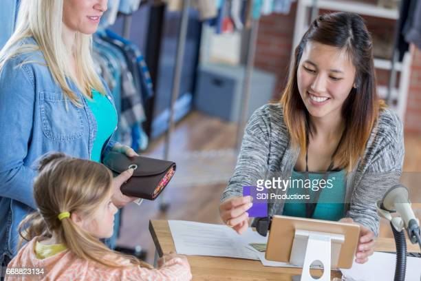 Boutique employee scans customer's loyalty card or credit card