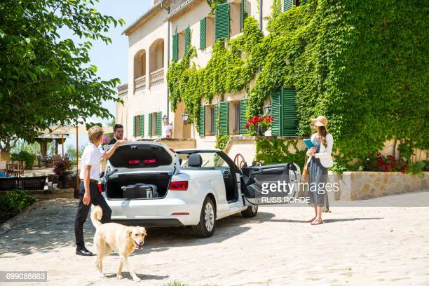 Boutique hotel porter getting luggage for couple arriving in convertible, Majorca, Spain