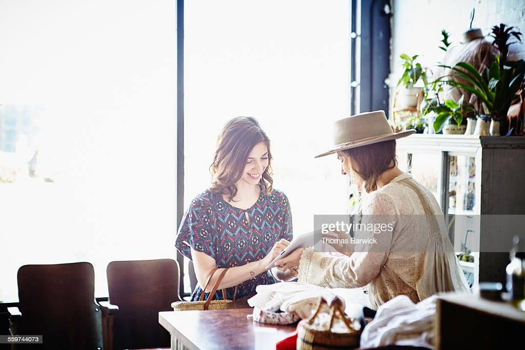 Boutique owner helping customer with purchase : Stock Photo