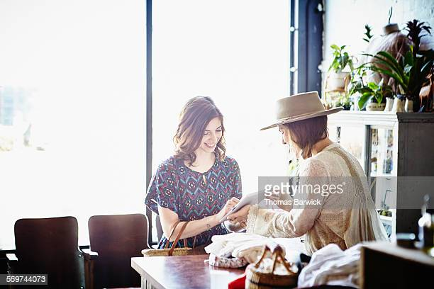 Boutique owner helping customer with purchase