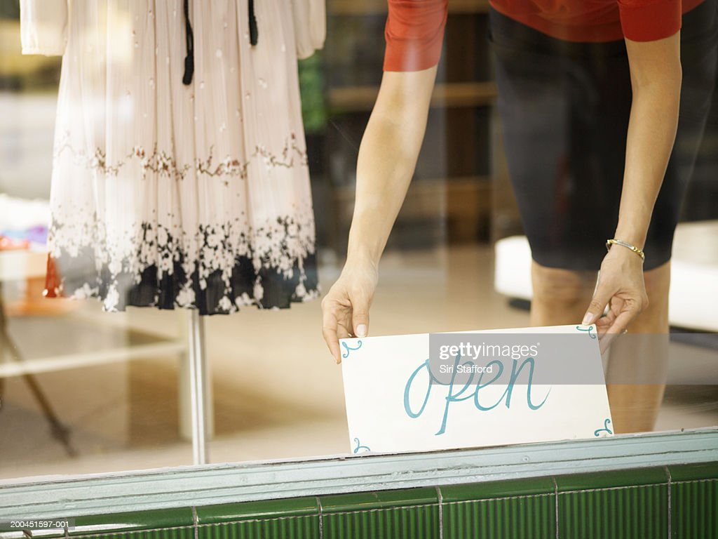 Boutique salesperson placing open sign on window : Stock Photo