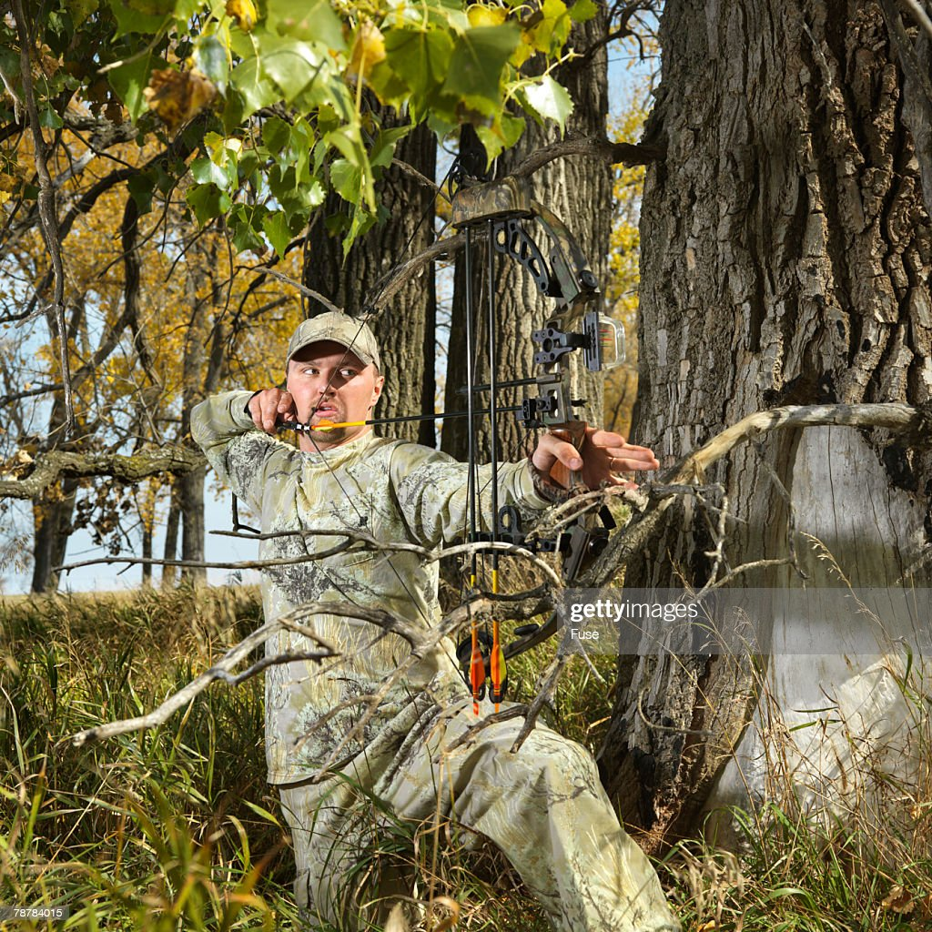 Bow Hunter Aiming Compound Bow in Trees