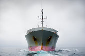 Bow of a pink and grey cargo ship.