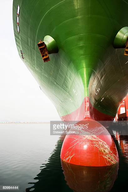 Bow of a red and green cargo ship.