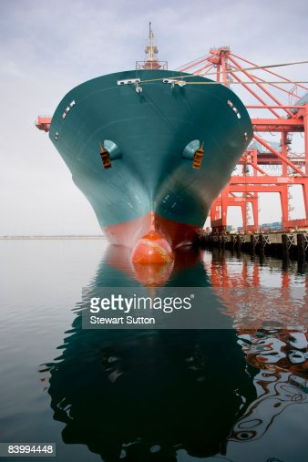 Bow of a red and teal cargo ship. : Stock Photo