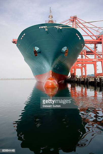Bow of a red and teal cargo ship.