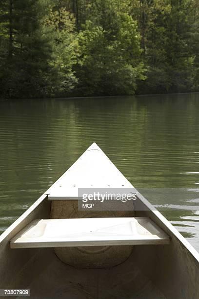 Bow of aluminium canoe on woodland lake (personal perspective)