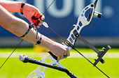 A man is shooting with a recurve bow during un open archery competition. Hands and bow only