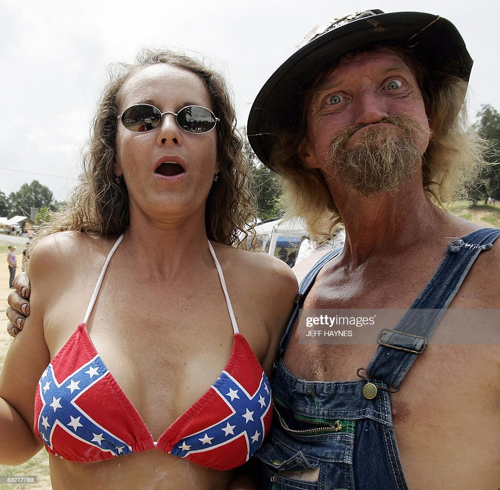 'L Bow', the unofficial games supervisor, hugs a local Georgian woman wearing a Confederate flag bikini before the start of the 10th annual 'Redneck Games' 09 July 2005 at Buckeye Park in East Dublin, Georgia. Started 10 years ago as a spoof of the 1996 Atlanta Olympics attended by about 500 people, the event was attracting 10,000 by 2001 and reached an estimated 15,000 in 2005. AFP PHOTO/Jeff HAYNES