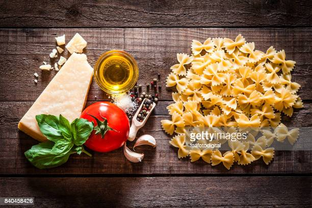 Bow tie pasta with ingredients on rustic wooden table