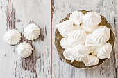 Delicious and plain white vanilla meringue cookies in silver traditional  bowl