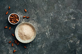 Bowl of almond flour and bowl of almonds from top view, copy space. Gluten-free flour.