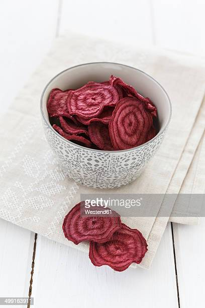 Bowl of beetroot chips on cloth and white wooden table