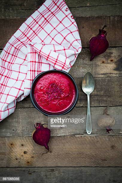 Bowl of beetroot soup garnished with beetroot sprouts on dark wood