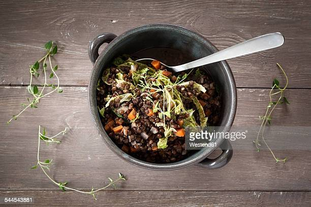 Bowl of beluga lentil stew with savoy, tomatoes and carrots