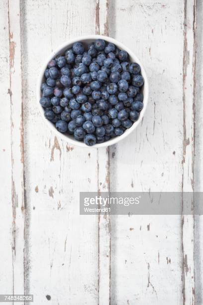 Bowl of blueberries on white wood
