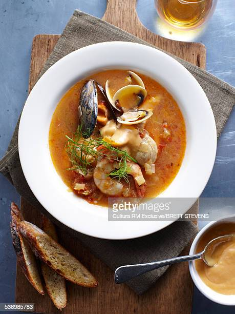 Bowl of bouillabaisse with dill garnish on chopping board