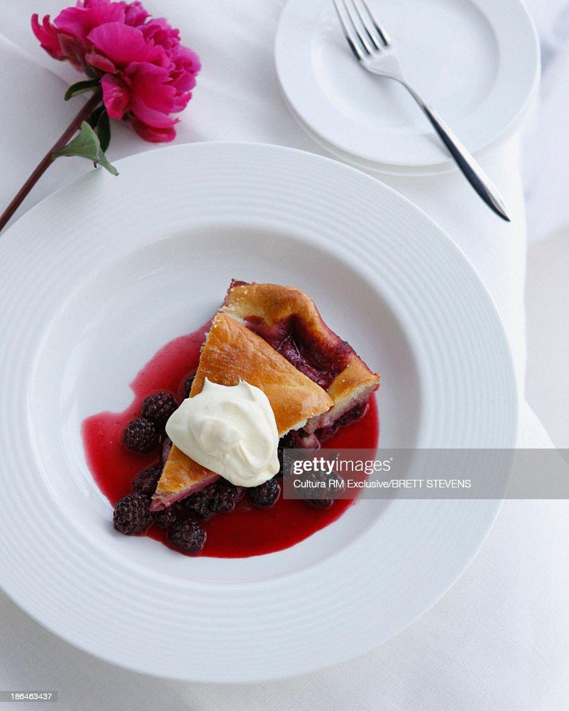 Bowl of bramble pie with double cream