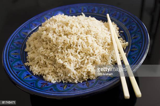Bowl of brown wholegrain rice and chopsticks Rice has become an expensive commodity as its in short supply