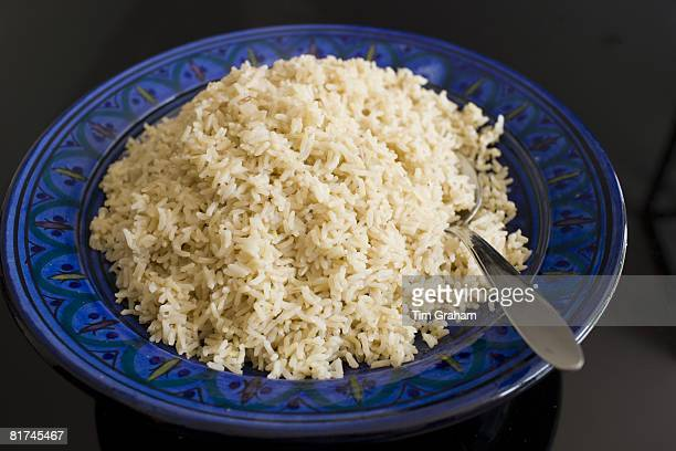 Bowl of brown wholegrain rice and spoon Rice has become an expensive commodity as its in short supply