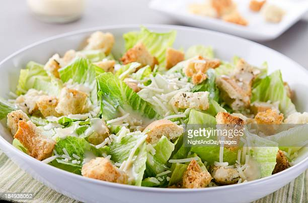 A bowl of Caesar Salad with croutons and cheese on table