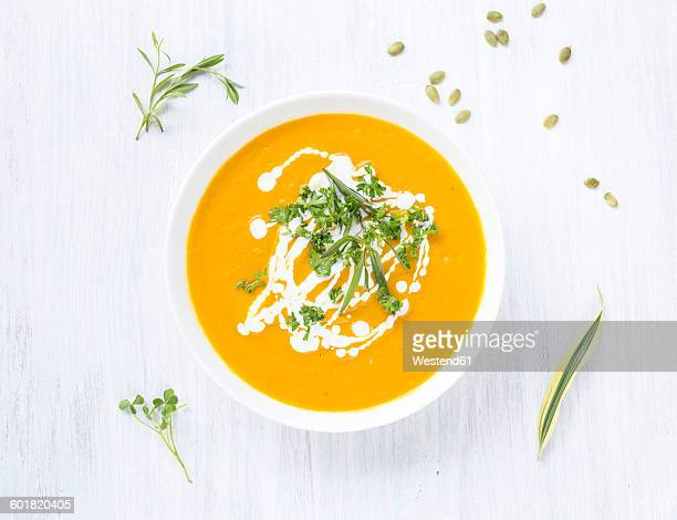 Bowl of carrot pumpkin soup with topping