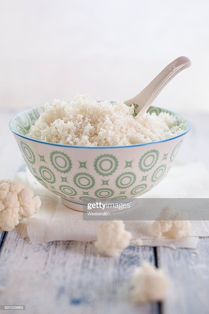 Bowl of cauliflower rice and cauliflower florets on cloth and wood