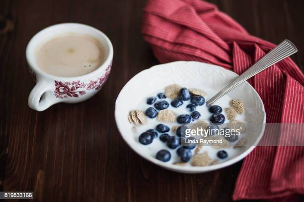 Bowl of cereal with blueberries and a cup of coffee