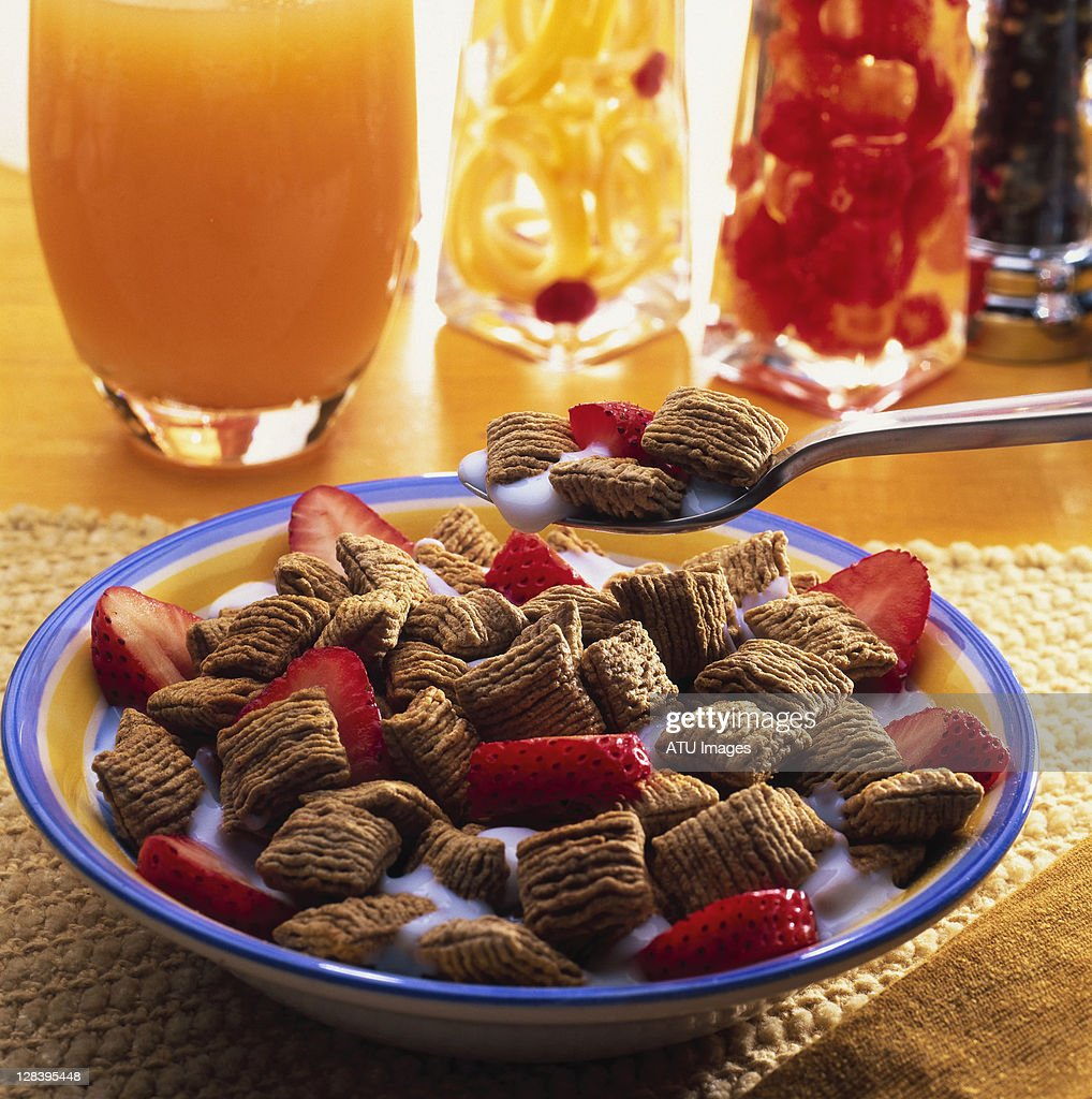 Bowl of cereal with strawberries orange juice : Stock Photo