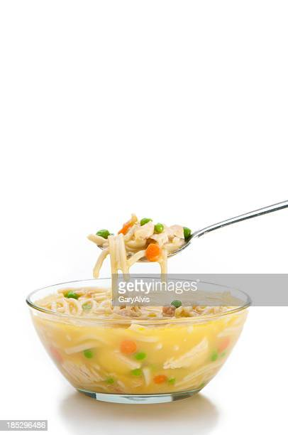Bowl of chicken noodle soup with spoon on white background