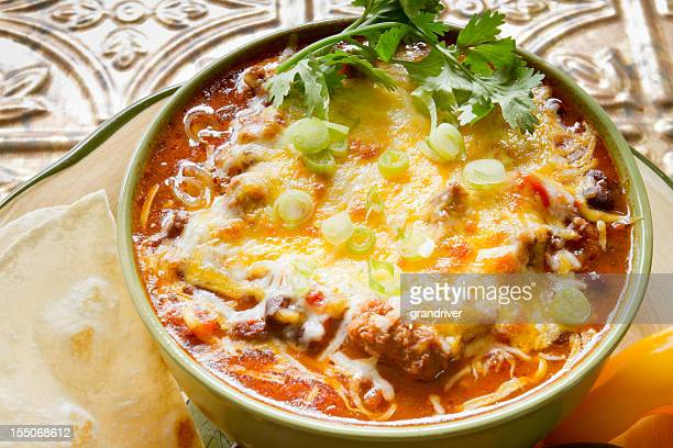 Bowl of Chili with Shredded Cheese and Flour Tortilla