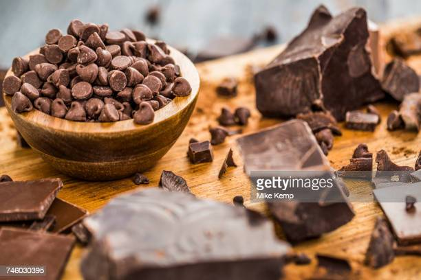 Bowl of chocolate chips and various chocolate pieces on cutting board