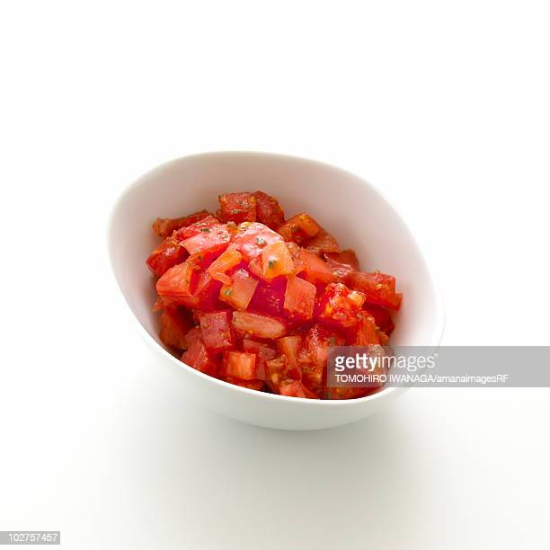 Bowl of chopped tomato, white background