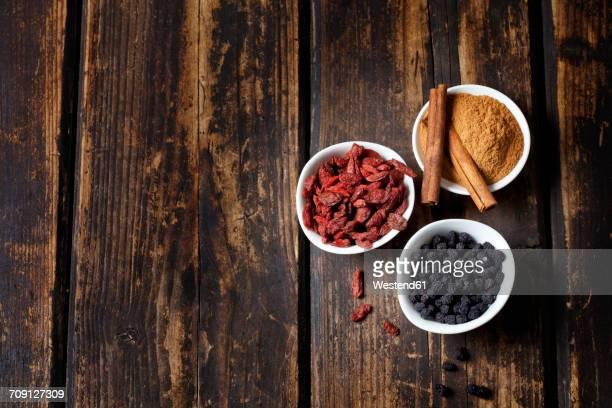 Bowl of cinnamon powder with cinnamon sticks, goji berries and chokeberries on wood