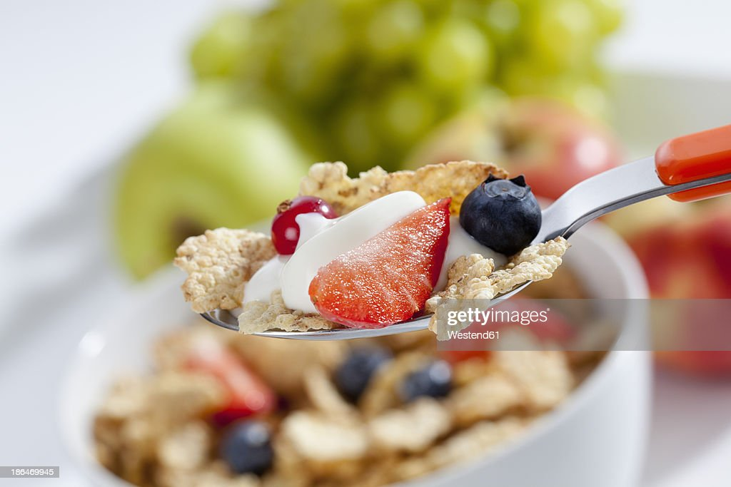 Bowl of cornflakes with various fruits, close up