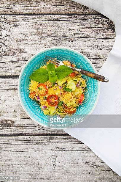 Bowl of couscous salad on wood
