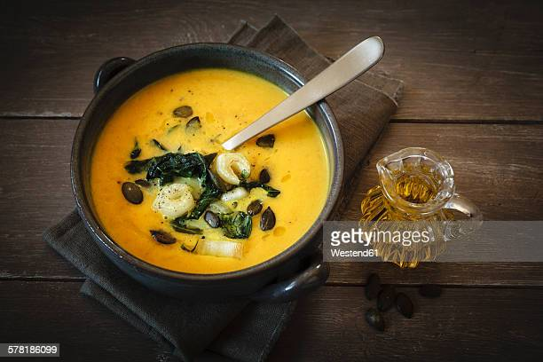 Bowl of creamed pumpkin soup with fried Chinese cabbage and pumpkin seed